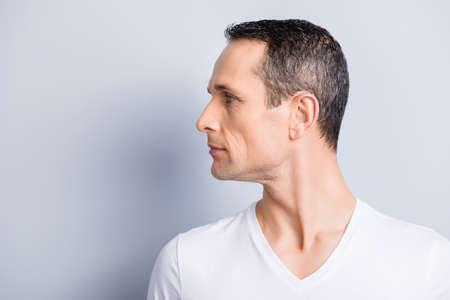 Retrato con espacio de copia, lugar vacío para el producto, anuncio de un hombre atractivo y elegante con el perfil volteado hacia un lado, que tiene una piel seca y engrasada ideal, aislada sobre fondo gris