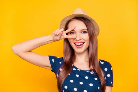 Portrait of cheerful, funny, positive, pretty, comic, funny, laughing girl in polka-dok t-shirt, gesturing v-sign near eye, having fun, isolated on yellow background