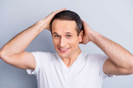 Portrait of shaven, experienced, neat, trendy, brunet, positive man holding two hand on head, touching his perfect hair, looking at camera, isolated on grey background