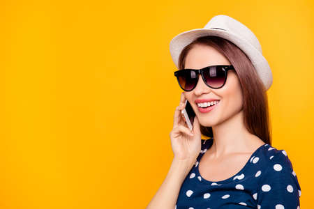 Portrait with copy space of charming, cool, pretty, sexy girl in black glasses, holding smart phone near ear, speaking with friends, having call from her lover, isolated on yellow background
