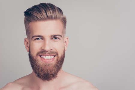 Schließen Sie herauf Porträt des netten hübschen attraktiven aufgeregten erfüllten emotionalen groben freundlichen attraktiven erstaunlichen Machos mit dem stilvollen modernen Haarschnitt, der auf grauem Hintergrundkopieraum lokalisiert wird