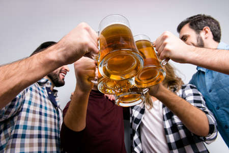 Diversity holiday recreation leisure vacation weekend victory concept. Low-angle cropped close up photo of four excited cheerful crazy careless fellows clinking mug on beer Stockfoto