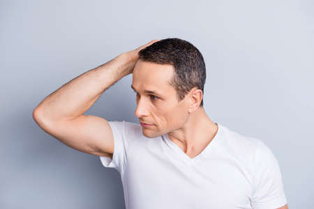 Half turned face of trendy, experienced, trendy, neat, stylish man, looking to the side, holding hand on head, correcting, fixing his hair, isolated on grey background Stock Photo