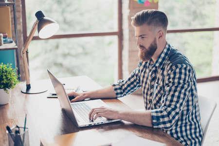 Half-faced Porträt des starken ernsten überzeugten hübschen intelligenten nachdenklichen klugen Managers, der über die Internetverbindung sitzt am Arbeitsplatzarbeitsplatz mit Kollegen in Verbindung steht