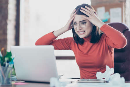 Modern technology financier economist people person concept. Hulf-turned portrait of sad unhappy upset disappointed journalist economist business lady holding head on hands looking at screen monitor
