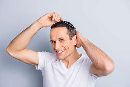 Neat, trendy, experienced, stylish, brunet, positive man looking at camera, combing, fixing, correcting his hair with hairbrush, holding hand on head, isolated on grey background