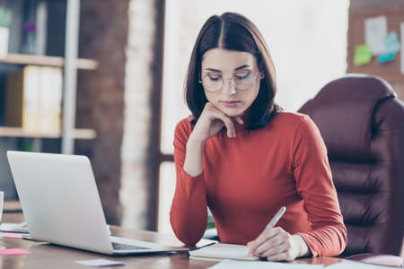 Pensive puzzled smart clever attractive focused journalist writing article for magazine