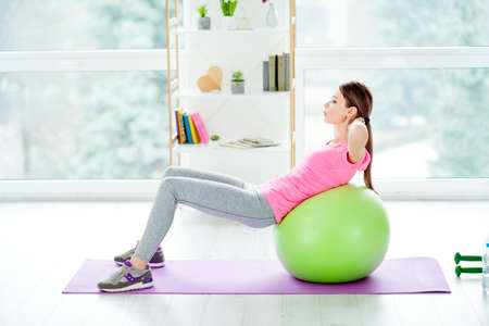Profile side view photo of concentrated focused aimed purposeful energetic woman using green fit ball for doing crunches wearing tight leggings casual pink tshirt white light studio club gym Stock Photo