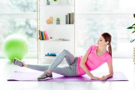 Side photo of purposeful enduring charming strong powerful beautiful blonde girl with ponytail hairdo modern stylish outfit doing exercise for inner tights lying on the floor on purple mat Imagens - 98220939