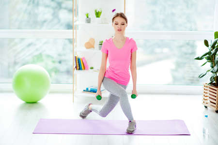 Front view portrait of powerful active focused beautiful energetic attractive woman holding green dumbbells in hands doing sit-ups standing on purple mat training in light modern white studio club gym