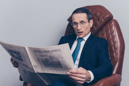 Rich reaction bad news open mouth unbelievable unexpected look facts press workstation executive corporate headline investments investor. Astonished speechless handsome banker holding newspaper