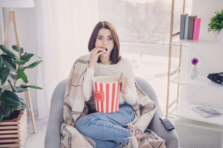 Portrait of pretty, charming, stylish, exciting girl with modern hairstyle putting pop corn in her open mouth watching spectacular film, covered with plaid, wearing denim outfit, jeans and pullover Foto de archivo - 98221865