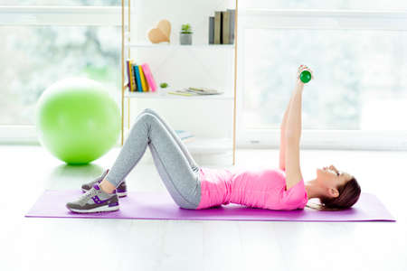 Profile view photo of charming strong purposeful enduring beautiful slim slender girl lying on purple mat holding putting hand up with dumbbells wearing tight modern stylish outfit white light room