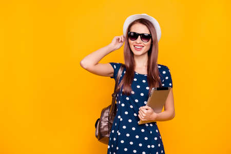 Cheerful, charming, positive, pretty girl with rucksack on shoulder, having, using tablet, holding white hat on her head, going for a walk, isolated on yellow background