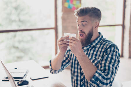Sad upset ill handsome attractive coughing with high temperature closed eyes  manager business businessman freelancer feeling discomfort using paper tissue checkered casual shirt light modern office