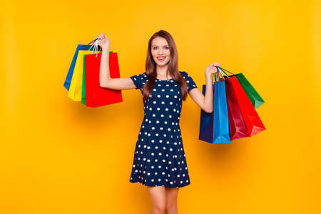 Attractive, charming, pretty, happy girl bragging about purchases, having colorful shopping packets in two hands, she bought a lot of things and spend much money, isolated on yellow background Stock Photo