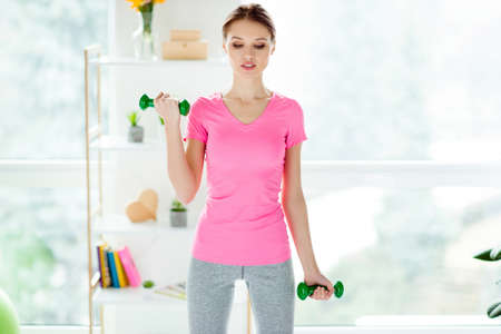 Portrait of exhausted tired strong purposeful attractive focused confident self-assured charming woman clothed in sportive outfit doing exercises holding green dumbbells training hands and arms