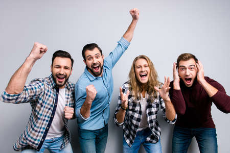 Cheerful funky joyful buddies raise hands fists, checkered casual clothes, isolated on gray background
