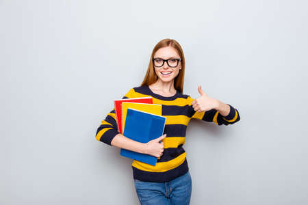 Academic exam copybook people teacher tutor fun joy enjoy concept. Portrait of pretty cheerful joyful rejoicing cute lovely teenager showing thumb-up holding book isolated on gray background
