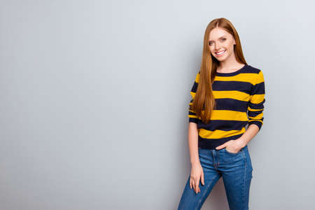 Portrait of pretty cute lovely charming stunning fit slim slender gorgeous confident wearing yellow and black striped pullover tight jeans keeping hands pocket isolated on gray background copy-space