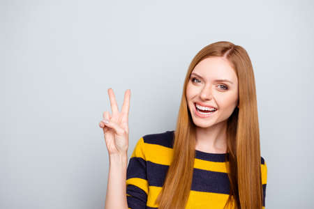 People positive funky dream dreamy rest relax weekend concept. Portrait of excited lovely beautiful with toothy beaming smile girl demonstrating two fingers isolated on gray background copy-space