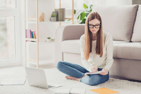 Academic campus degree brainstorming pupil highschool people concept. Concentrated focused cute clever thinking pondering pensive girl doing homework in house on the white fluffy carpet