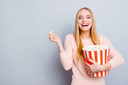 Portrait of charming lovely cute relaxed carefree delightful rejoicing beautiful with long blond hair toothy beaming smile teen age girl watching movie at home eating popcorn isolated gray background