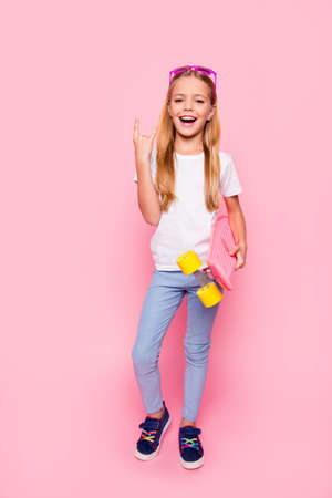Trendy fashion style stylish funtime concept. Vertical full-size full-length portrait of laughing cute sweet adorable lovely charming girl denim jeans white tshirt blue shoes isolated pink background Stockfoto