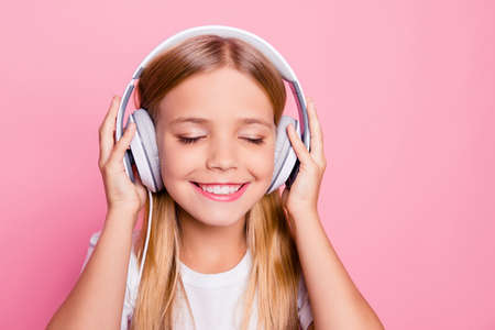 Modern technology concept. Close up portrait of cute tender sweet lovely with beaming toothy smile closed eyes girl enjoying nice tune on headphones isolated on bright pink background Stock Photo