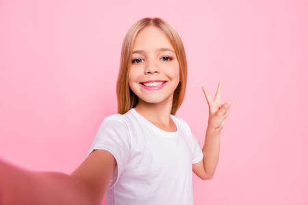 Close up portrait of cute lovely sweet funky adorable beautiful charming with toothy with blonde hairstyle beaming smile girl making v-sign gesture white tshirt isolated on pink background Stock Photo
