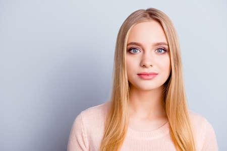 Portret słodkiej uroczej, delikatnej, delikatnej, niewinnej, spokojnej dziewczyny z długimi, gładkimi, prostymi, naturalnymi blond fryzurami, duże niebieskie oczy ubrane w beżowy zimowy ciepły sweter na szarym tle