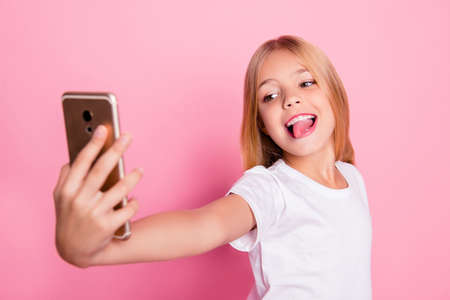 Addiction lifestyle leisure style trend play game concept. Close up portrait of cute lovely sweet charming with toothy smile taking selfie girl on mum's phone isolated on pink background Standard-Bild