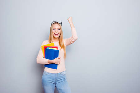Assistant knowledge hipster smart clever trainee learning campus embrace lecture jeans denim hipster people concept. Portrait of excited cheerful girl raising fists up isolated on gray background