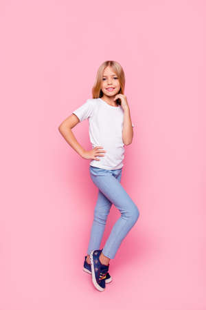 Vertical full-length portrait of cute sweet lovely adorable beautiful with beaming toothy smile charming pre teen girl holding hands near chin on waist standing isolated bright vivid pink background Foto de archivo
