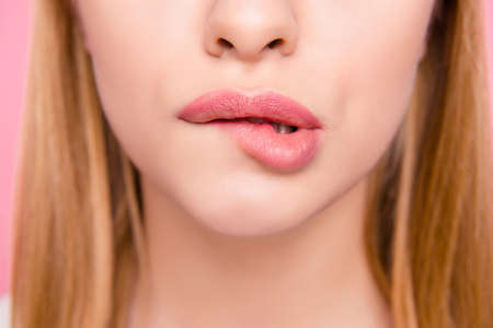 Fillers plump plastic herpes surgery concept. Close up cropped photo of big full natural with lipgloss lips teeth biting lips blonde hair hairstyle isolated on background