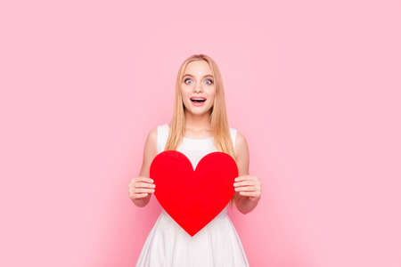 Relationship health cardio care people concept. Portrait of glamorous astonished shocked amazed wondered excited beautiful charming joyful girl demonstrating large heart in arms isolated on background