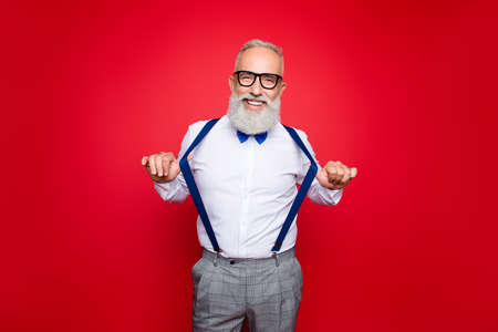 Portrait of elegant, confident, playful macho, old barber, stylist draw off suspenders with thumb fingers, looking at camera with beaming smile, isolated on red background Stock Photo