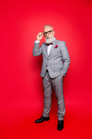 Portrait of cool, virile, harsh, perfect old man in checkered grey suit and eyewear, standing, isolated on red background, looking at camera, holding hand on eyelet of glasses on his face Stock Photo