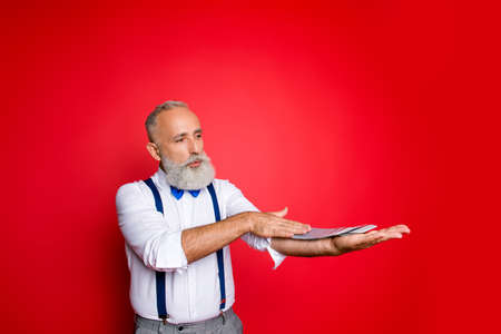 Professional, handsome, trendy, attractive old man with blue bowtie and suspenders spread deck of cards along the arm with one hand over red background, having pout lips, serious concentrated expression