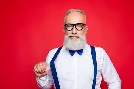 Portrait of elegant, confident macho, old barber, stylist draw off suspender with thumb finger, looking at camera with simper, isolated on red background