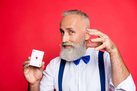 Portrait of attractive, handsome man with mysterious expression, half turned face, blue bowtie and suspenders, having joker in hand, gesturing with hand, making focus, isolated on red background Stock Photo