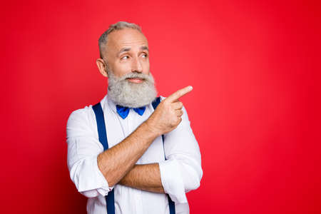 Portrait with copy space of minded, ponder, professional, retro stylist, barber with blue bowtie and suspenders pointing on empty place, product with forefinger, isolated on red background Banco de Imagens - 98977151