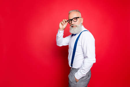 Portrait of cool, manly, fashionable old man holding hand in pocket and eyelet of glasses on his face, looking at camera with smirk, isolated on red background, having blue suspenders, pants