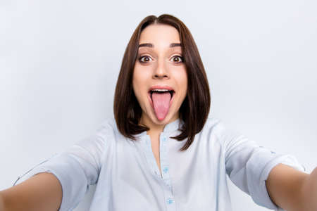 Self portrait of pretty, charming, comic, childish, funny girl with modern hairstyle gesture tongue out to the front camera shooting selfie with two hands, isolated on grey background