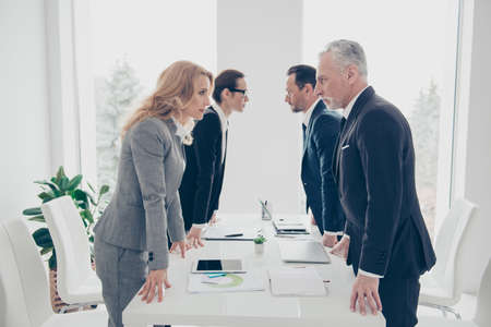 Business competition, four stylish business persons in suits having disagreement and conflict, standing together near desktop in front of each other, face to face with disrespect expression Stock Photo