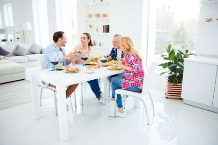 Full size portrait of beautiful cheerful girlfriends, handsome festive boyfriends in casual outfit sitting at the table with dishes, food, meals, wine, sharing bread having fun, domestic lifestyle Stock Photo