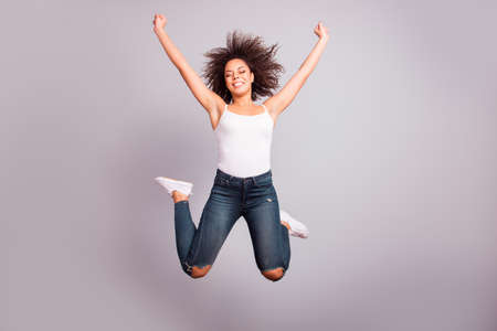 Full size portrait of cheerful, confident, attractive, funny, crazy, funky girl in jeans, sneakers, having fun, leisure, rest, relax, celebrating pass exams with close eyes over grey background