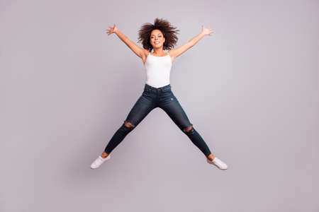 Full length, full size, fullbody portrait of cheerful crazy successful confident lucky charming pretty girl jumping with open hands and legs like star figure, isolated on grey background 写真素材