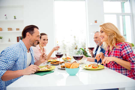 Side view portrait of cheerful, beautiful women and handsome stylish men gathering in house, apartment, room, festive company sitting at the table discussing, talking, enjoying, having fun, laughing