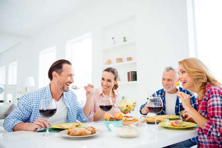 Beautiful cheerful girlfriends, handsome festive boyfriends in casual outfit sitting at the table with dishes, food, meals, wine, having fun, domestic lifestyle, holding forks with food near mouth Stock Photo